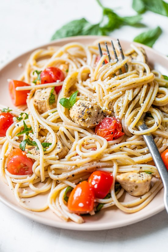 Spaghetti with Sauteed Chicken and Grape Tomatoes on a plate with a fork.