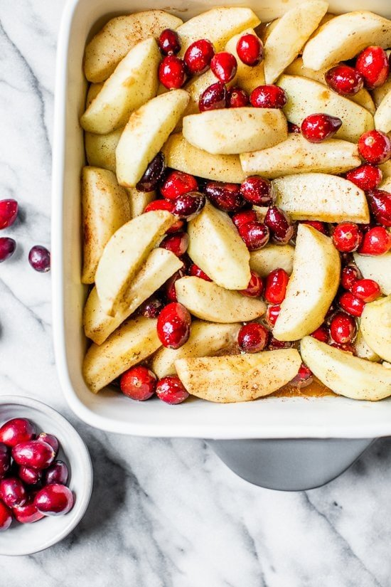 apples and cranberries in a baking dish.